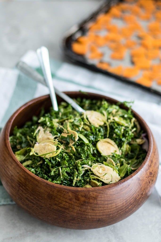 A bowl of shredded kale and very thinly sliced brussels sprouts, massaged with a citrus vinaigrette.