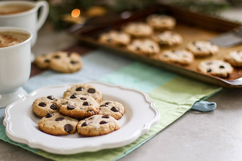 A plate of paleo chocolate chip cookies in front of a baking sheet of cookies.