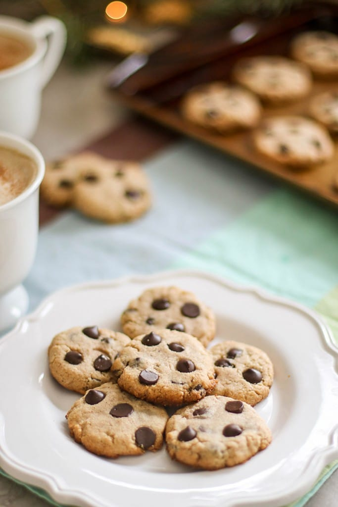 A white plate stacked with healthy paleo chocolate chip cookies, with mugs of coffee in the background.