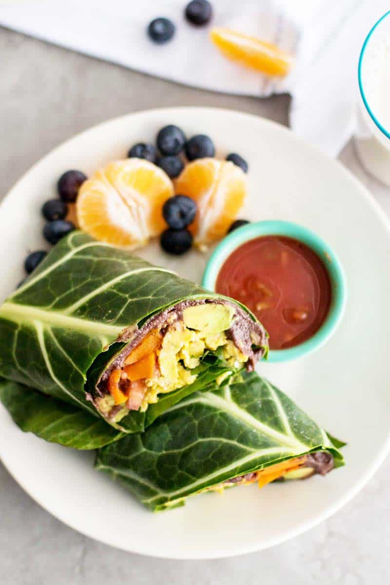 A top down view of a collard wrap breakfast burrito served with fruit and salsa.