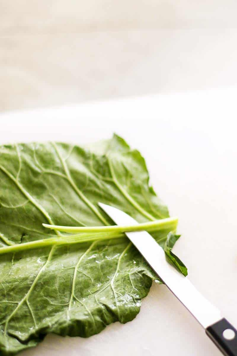 A leaf of kale on a cutting board with a knife removing the stem.
