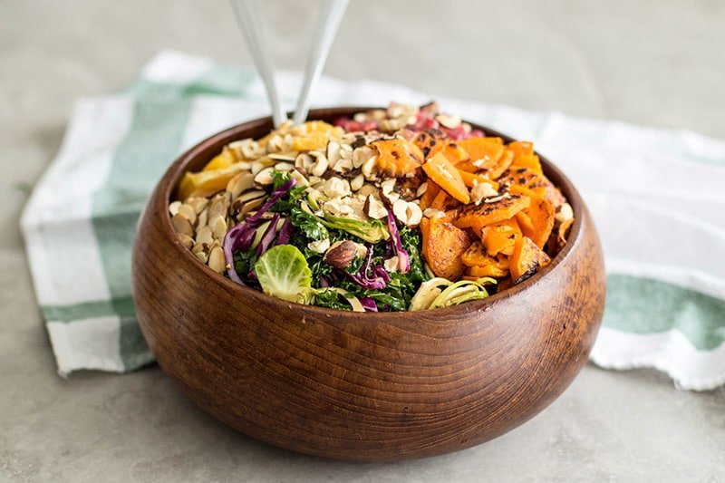 A side view of a wood salad bowl with a loaded kale and brussels sprouts salad.