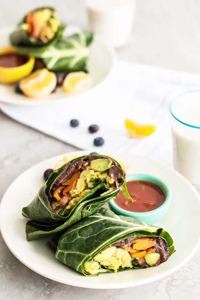 Two plates with breakfast burritos served with fruit.