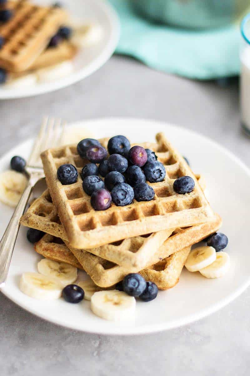 A stack of waffles with bananas and blueberries.