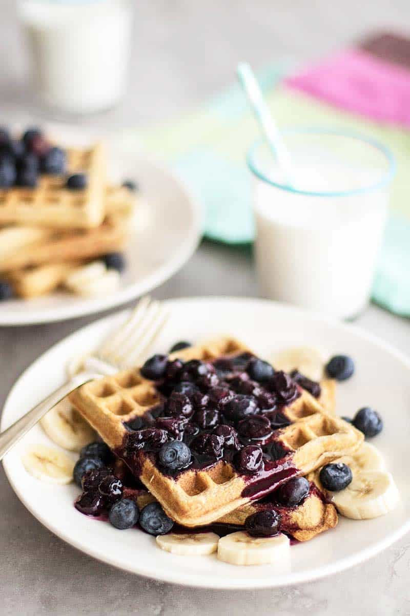 A stack of waffles topped with blueberry syrup.