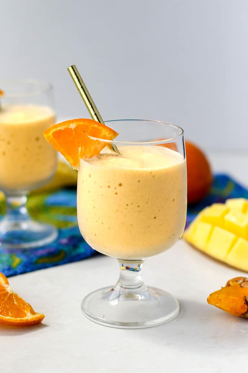 A gold turmeric smoothie in a glass garnished with an orange.