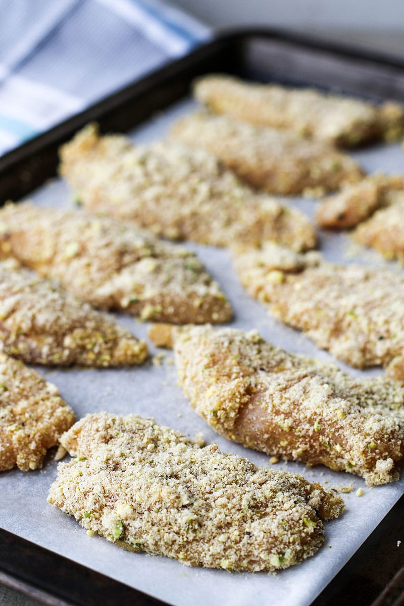 Pieces of chicken coated in egg and a pistachio flour.
