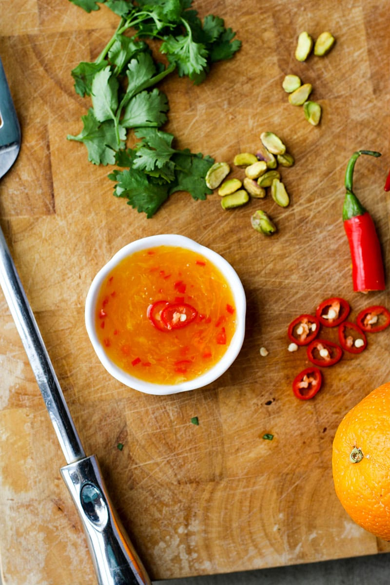 A cutting board with a ramekin of orange chili dipping sauce.
