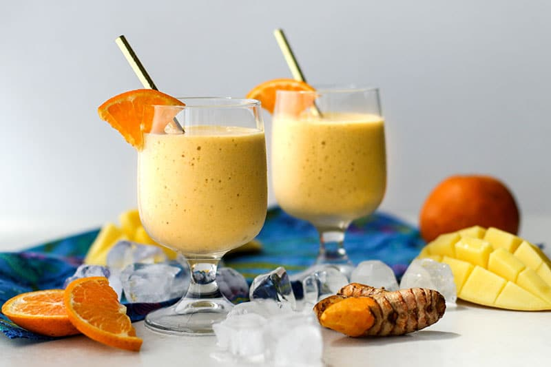 Two superfoods smoothies on a table with ice cubes and a piece of turmeric.