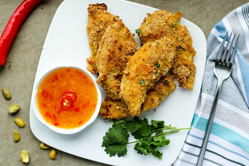 A plate of pistachio crusted baked chicken fingers with a ramekin of orange chili dipping sauce.