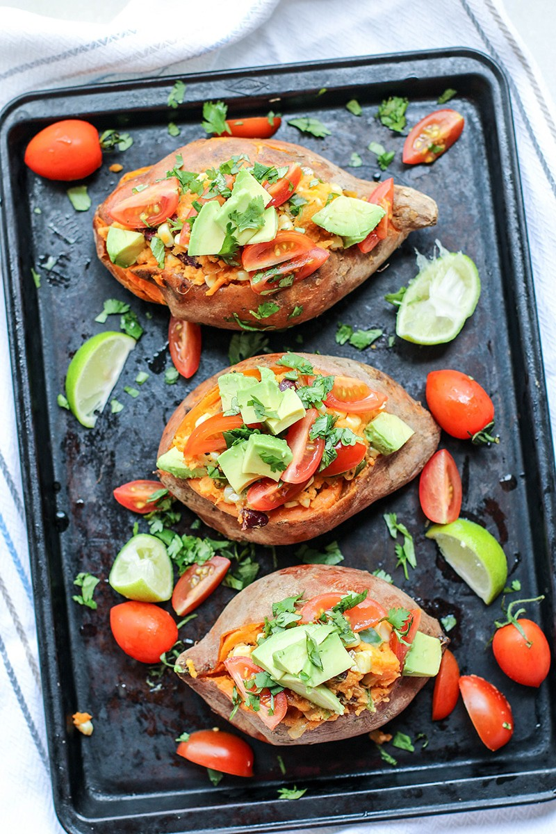 Baked sweet potatoes on a black baking tray topped with avocado, tomatoes, and cilantro.