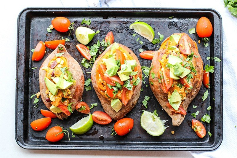 Sweet potatoes stuffed with beans and cheese and topped with avocado and salsa.