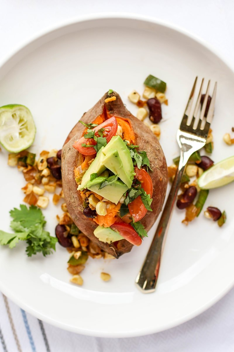 A stuffed sweet potato topped with avocado, cilantro, tomatoes and lime wedges.