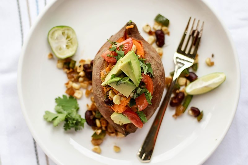 A Mexican stuffed sweet potato on a white plate.