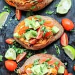 4 baked sweet potatoes on a black baking tray.