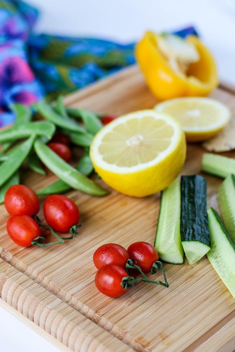 A cutting board with veggies prepared to dip.