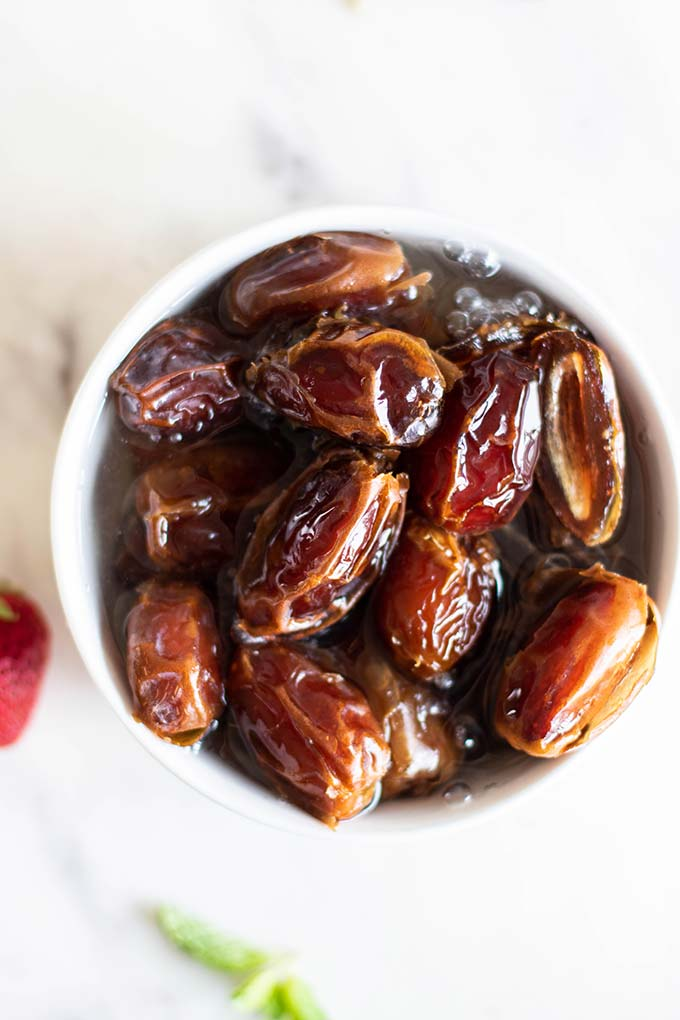 A bowl of medjool dates soaking in hot water.