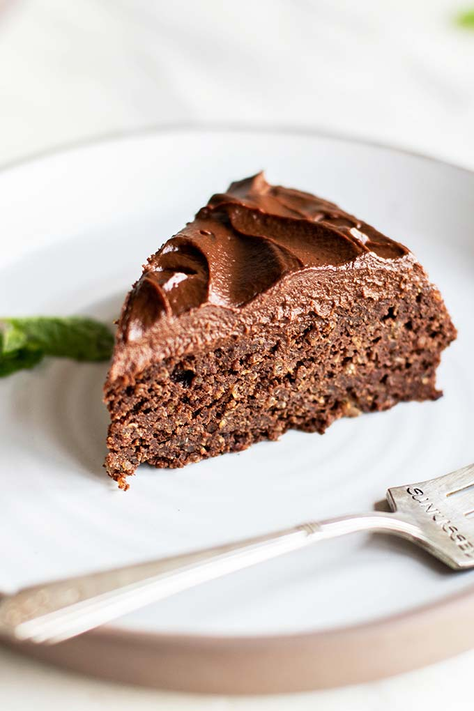 A slice of chocolate quinoa cake with a thick layer of sweet potato frosting.