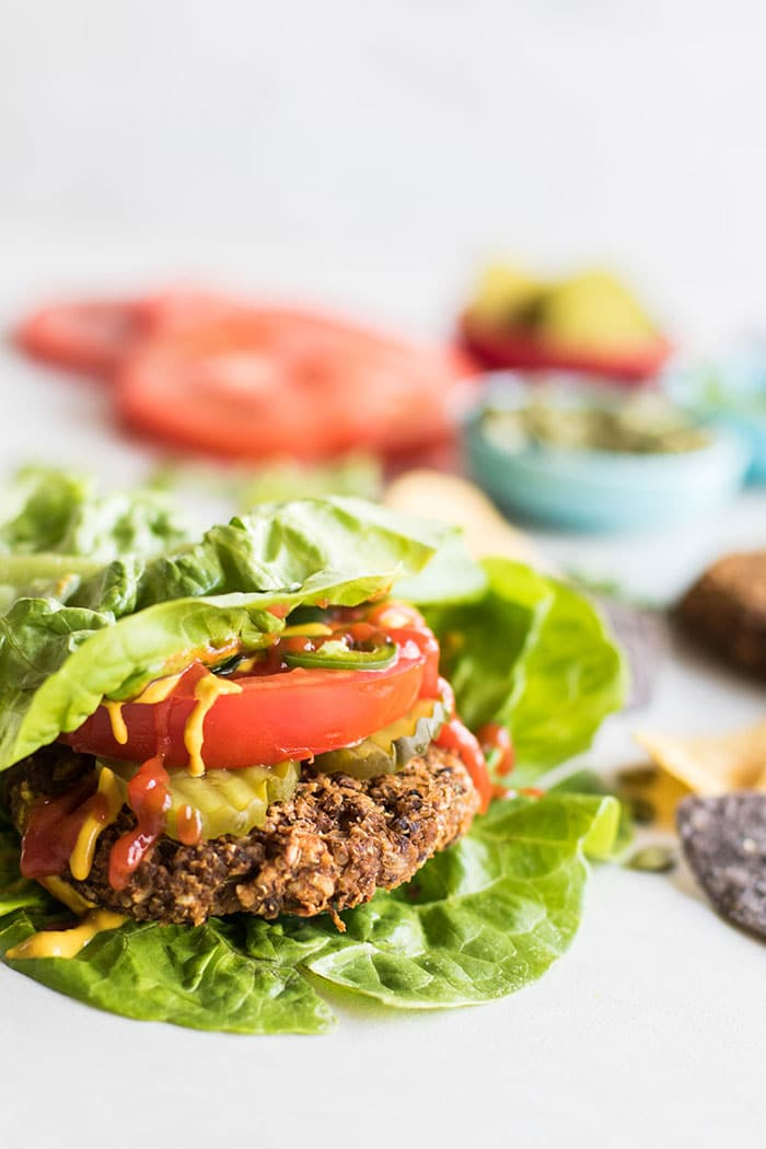 A pumpkin seed veggie burger wrapped in lettuce and topped with tomato and pickle.