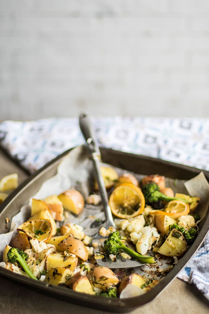 A roasting pan with veggies being scooped out.