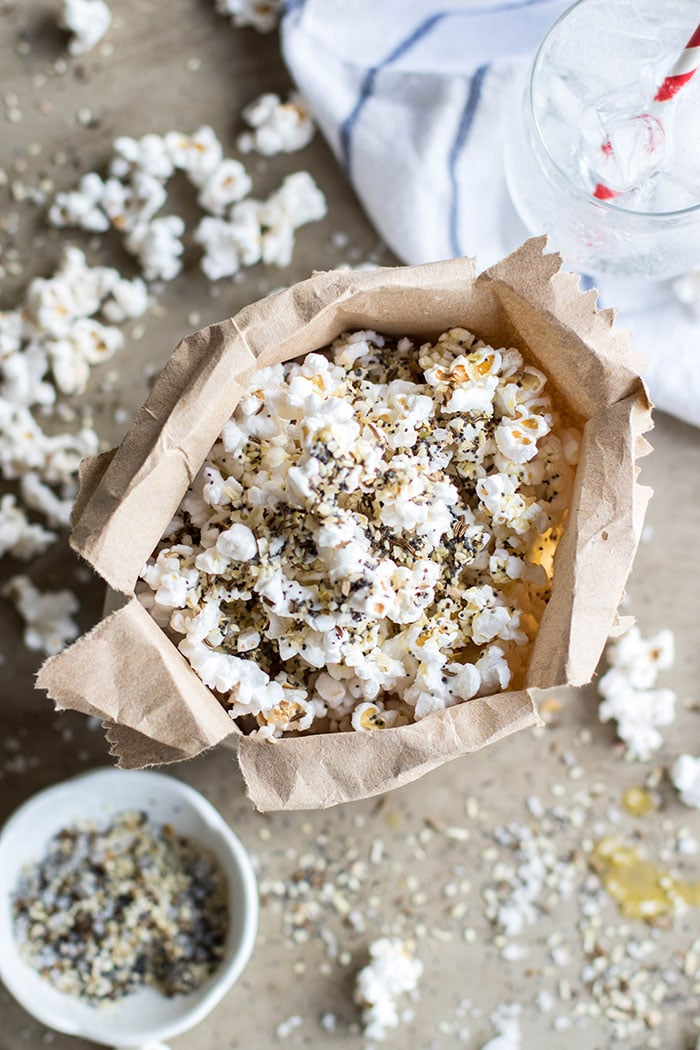 A paper bag shown full of popcorn covered in everything bagel spice.