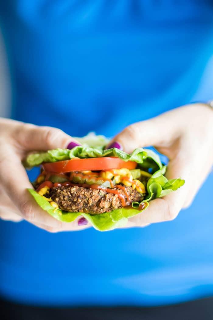 A pumpkin seed veggie burger wrapped in lettuce, held in hands.