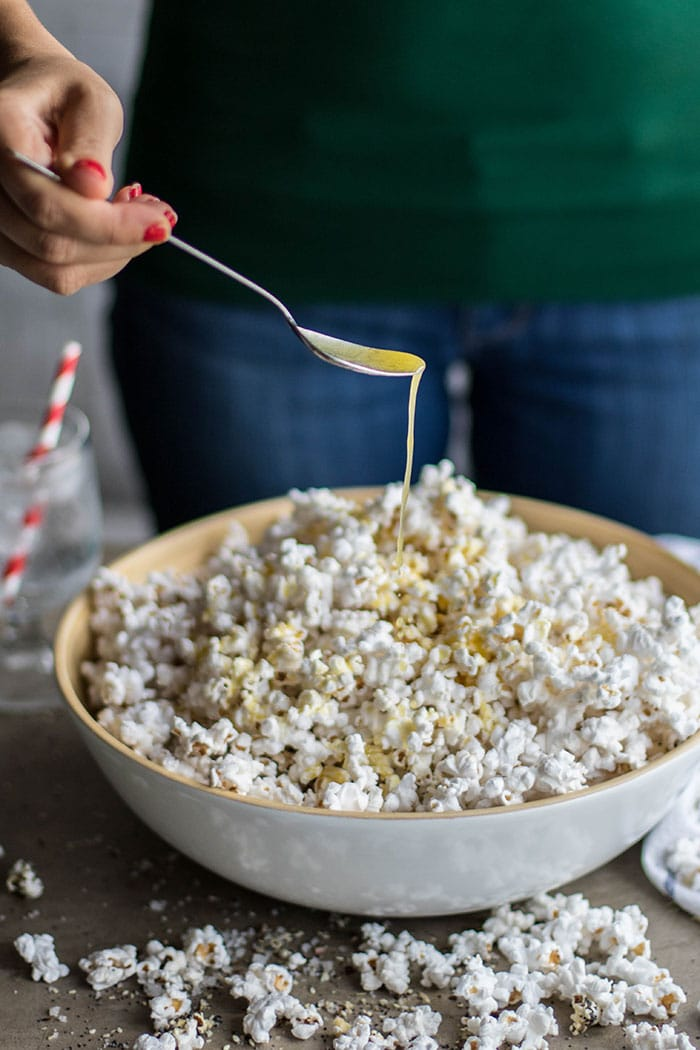 A bowl of popcorn, with Michelle drizzling on butter.