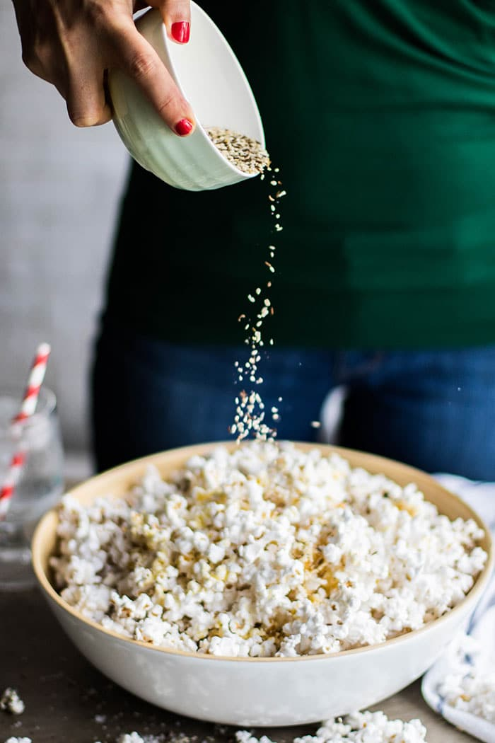 A bowl of popcorn with everything bagel spice being sprinkled on.