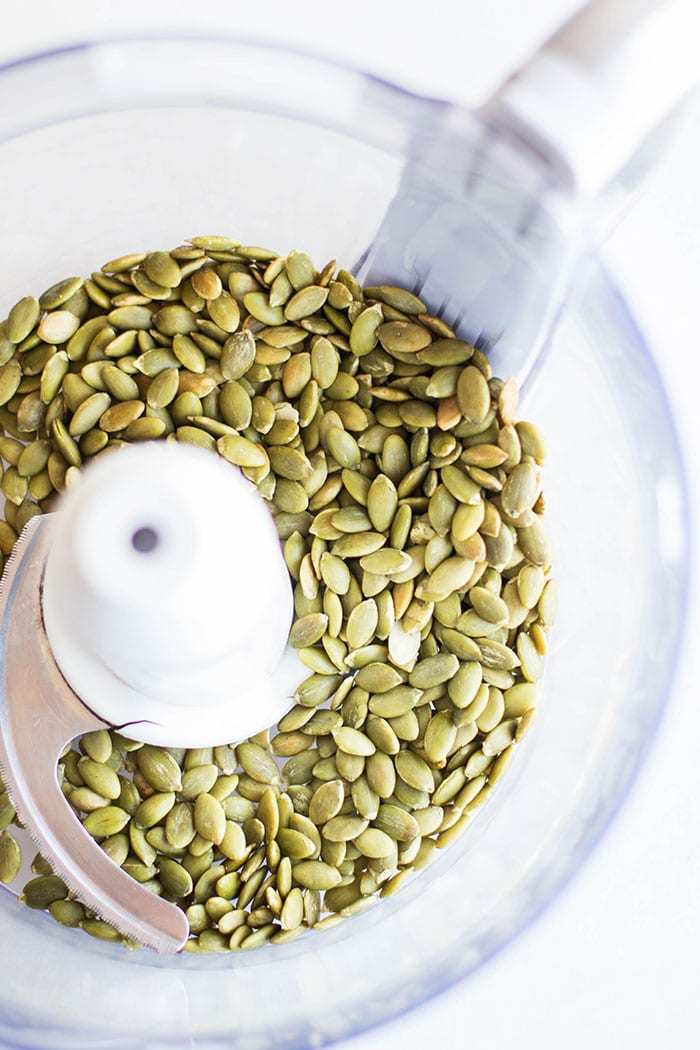 A food processor filled with pumpkin seeds.