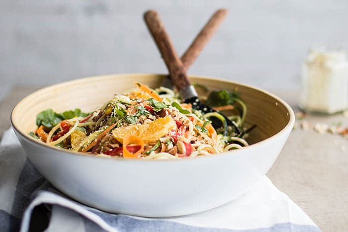 A fresh salad made with zucchini noodles, oranges, and a sesame dressing.