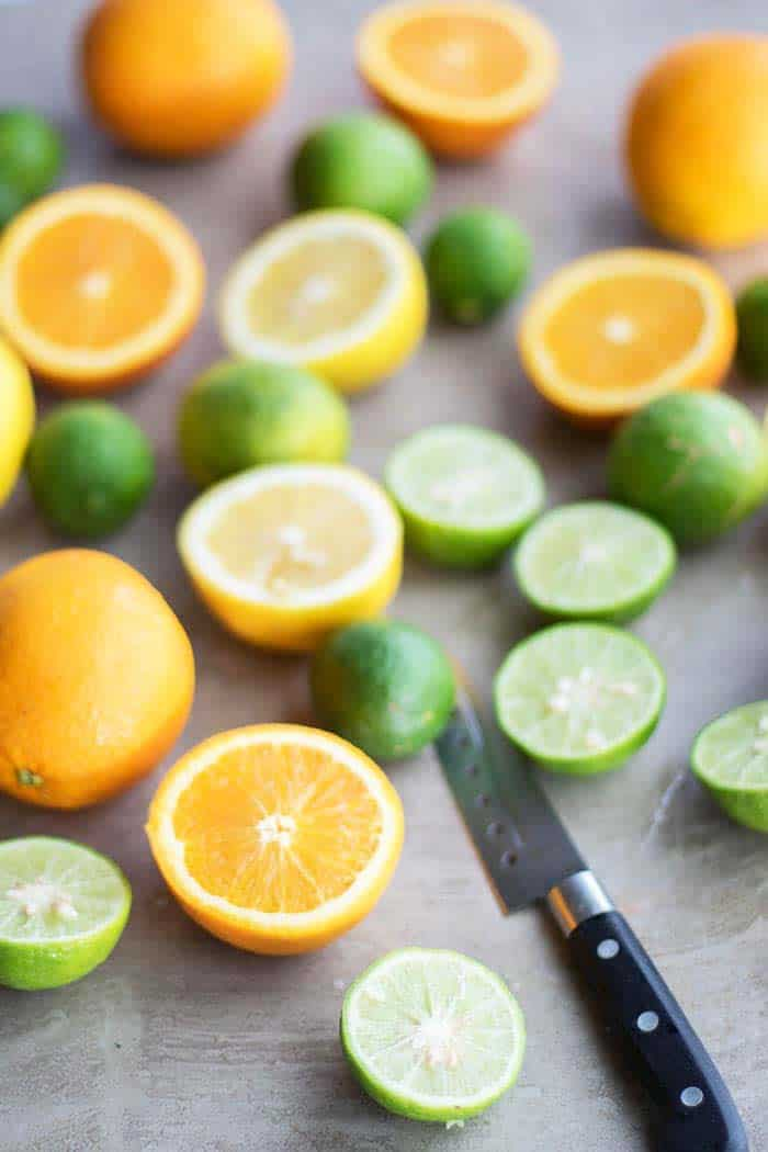 A cutting board covered in sliced citrus fruits.