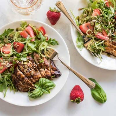 Grilled balsamic chicken on a salad of cucumber noodles with strawberries, sunflower seeds and sesame seeds.