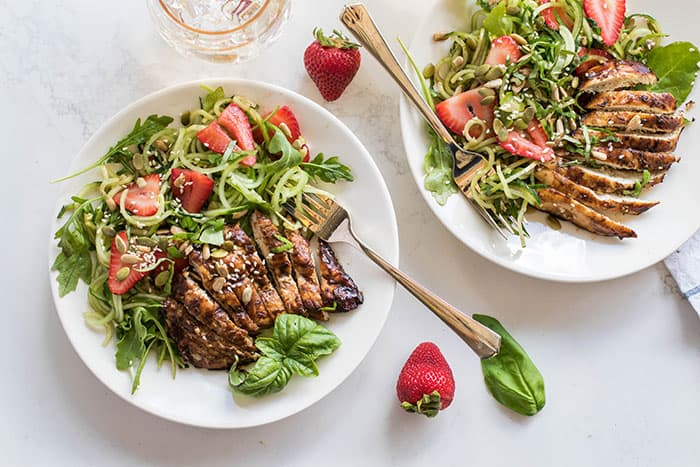 Two plates with grilled balsamic chicken over a strawberry cucumber salad.