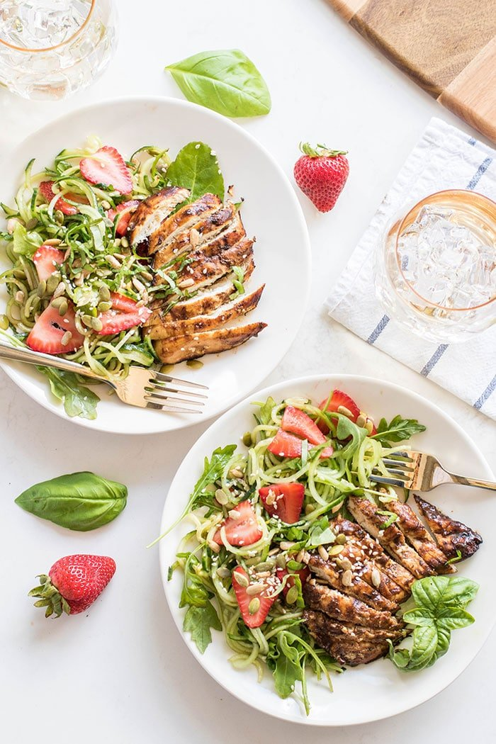 Two plates with a strawberry cucumber salad topped with grilled balsamic chicken.