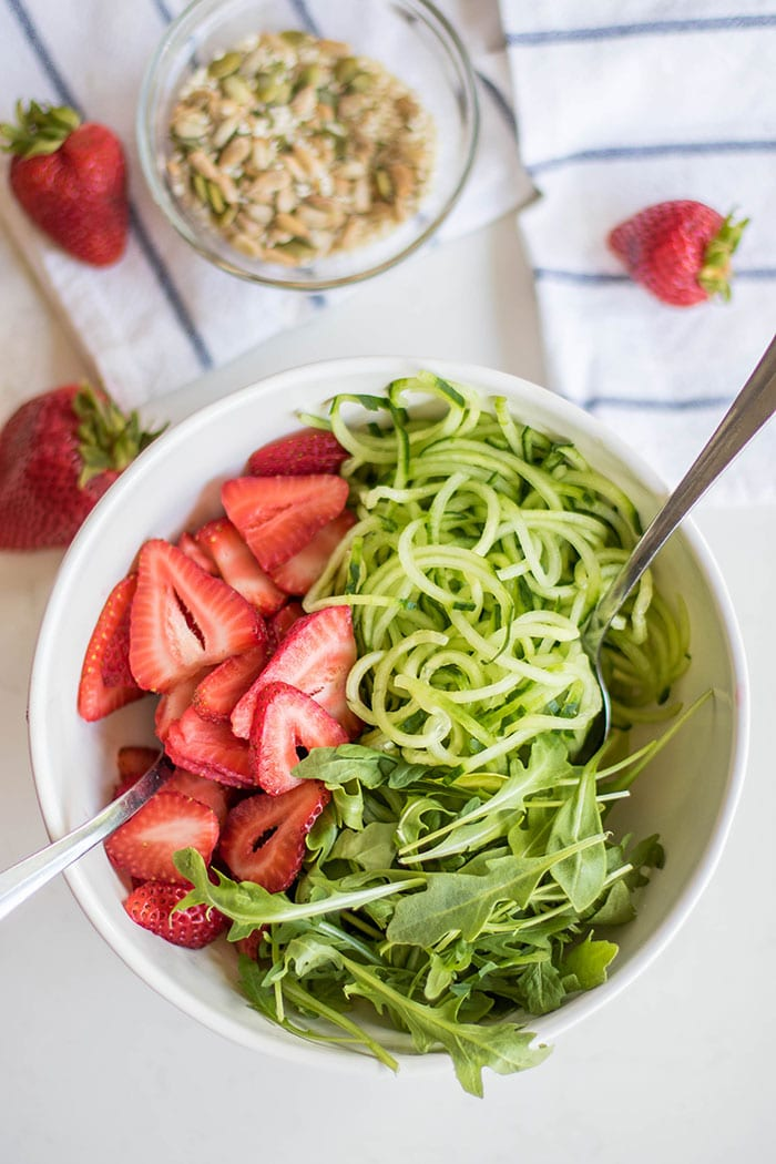 A bowl filled with spiralized cucumber, strawberries, and arugula.