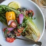 Grilled Romaine Salad topped with grilled peppers, onions, tomatoes and basil.