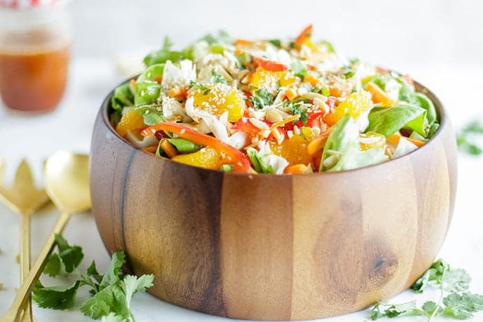 A wooden bowl packed with an Asian Cabbage Salad and a jar of asian cabbage salad dressing.