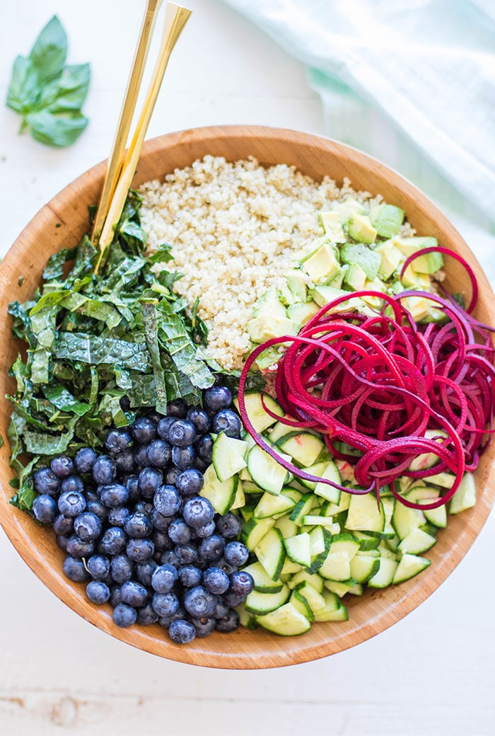A bowl filled with kale, quinoa, beets, cucumbers, avocado, and blueberries.