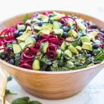 A bowl filled with a colorful blueberry kale salad.