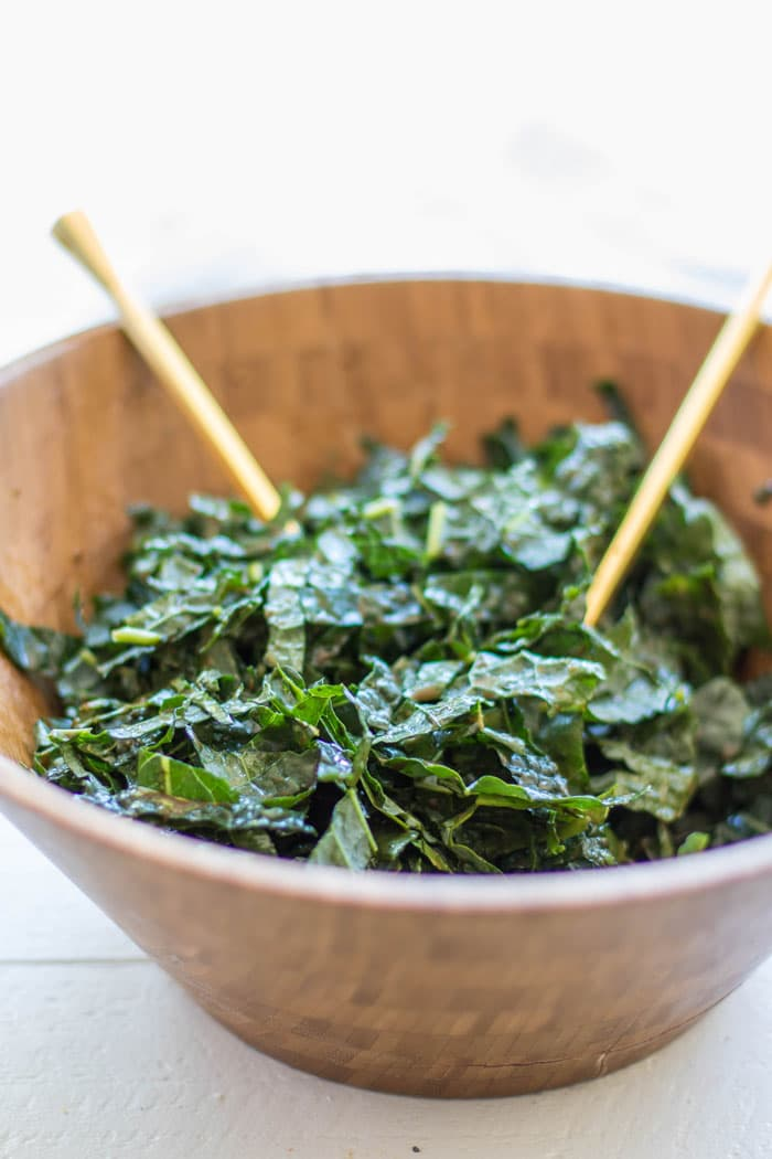 A bowl showing how to massage dressing into the kale to soften it.