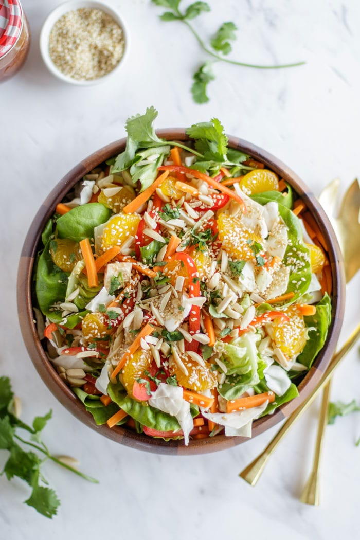 A wooden bowl filled with a crunchy asian cabbage slaw and loaded with toppings.
