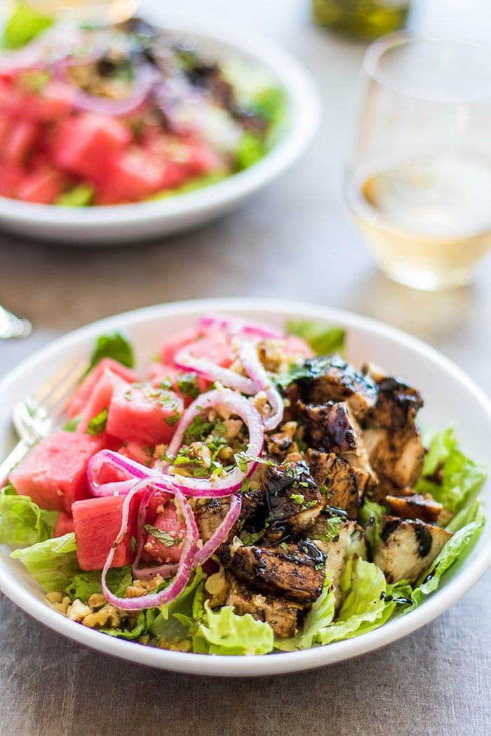 A plate piled high with a salad topped with grilled balsamic marinated chicken and watermelon.