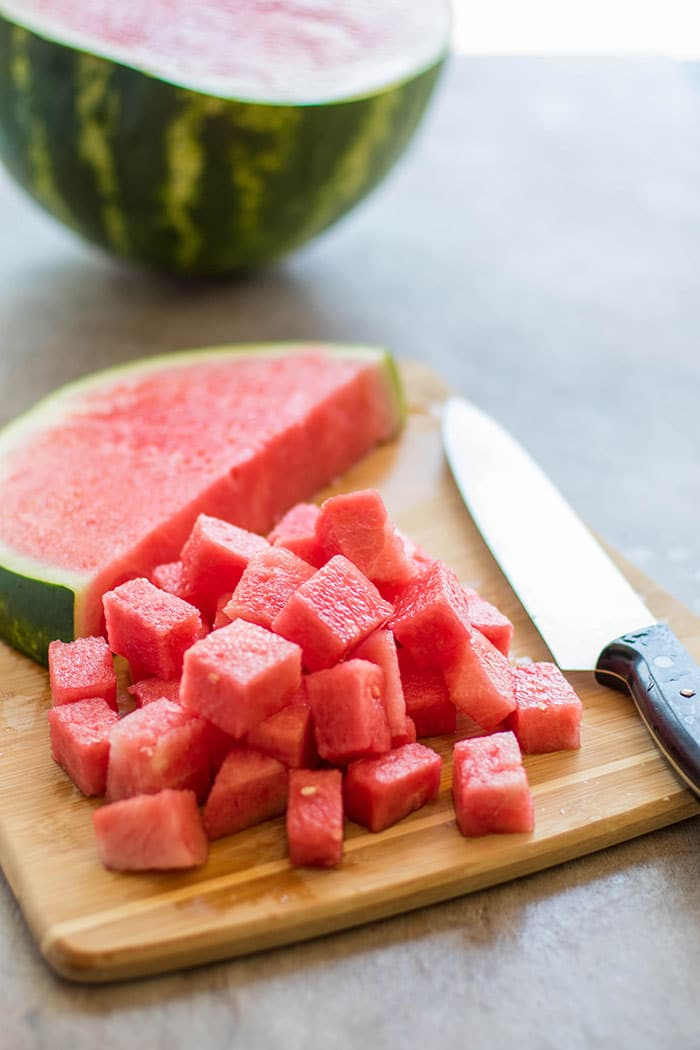 A cutting board with large chunks of watermelon cut up ready to be added to the salads.