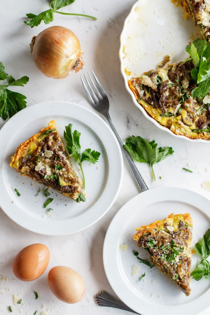 Two plates with slices of sweet potato frittata sprinkled with parsley.