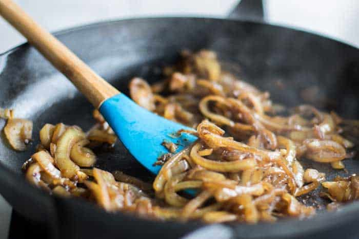 A skillet with caramelized onions, showing the dark and smooth texture once they are finished.