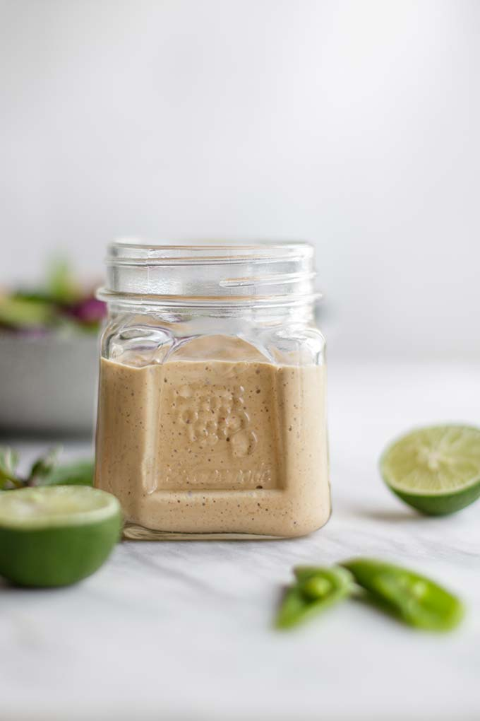 A side view of a jar filled with a homemade almond butter salad dressing.