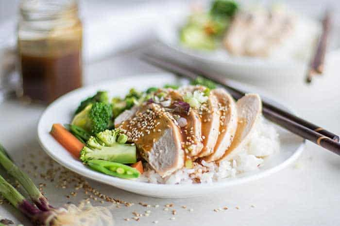 A plate with easy teriyaki sauce covering a plate of rice and chicken, sprinkled with sesame seeds.