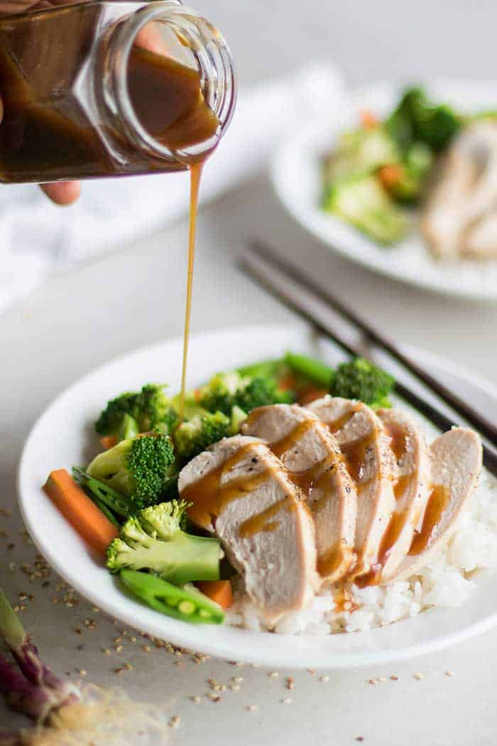 A plate of chicken, rice and vegetables, with soy free teriyaki sauce being drizzled on top.