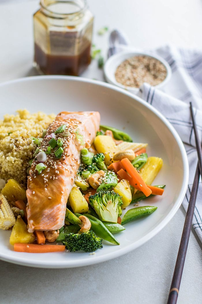 A plate with a piece of teriyaki salmon on top of a bed of millet and sauteed veggies.