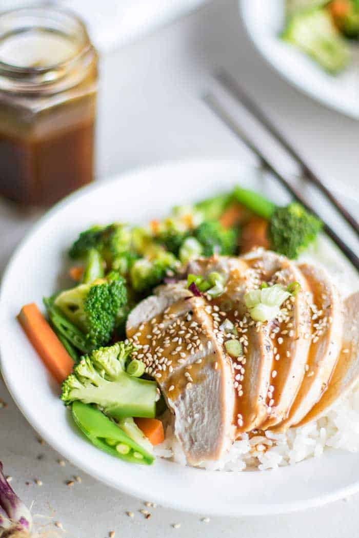 A plate with rice, vegetables, and chicken, drizzled with a soy free teriyaki sauce.
